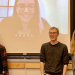 three graduate students in front of projector screen