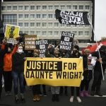 """protest outside police precinct with demonstrators holding a yellow and black banner that reads """"JUSTICE FOR DAUNTE WRIGHT"""""""