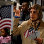 Muslim woman holding an American flag and raising her hand to take the citizenship oath