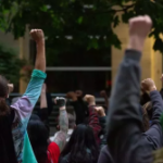 Protesters outside the Seattle West Precinct with their fists raised in the air