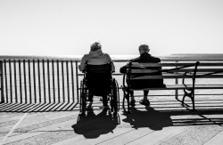 Two elderly adults sitting on a bench and wheel chair, looking out over the water