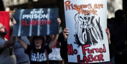 """Protestors holding signs that read """"Prisoners are people, No Forced labor"""" and """"End Prison Slavery"""""""
