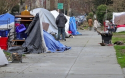 man walking along a sidewalk lined with tents in Seattle