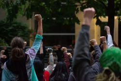 Protestors outside the Seattle Police Department's West Precinct with fists raised