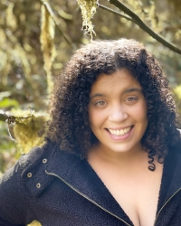 Image: Maxine Wright, a Black, light-skinned woman with curly hair, stands in the foreground smiling into the camera, with mossy trees as the backdrop