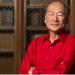 David Takeuchi in a read shirt against a bookshelf backdrop