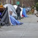 man walking along a sidewalk lined with tents in Seattle